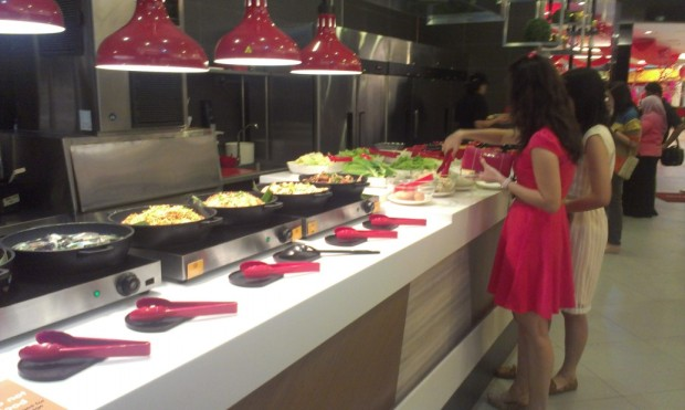 some cooked chicken, fish, rice and noodle dishes in foreground