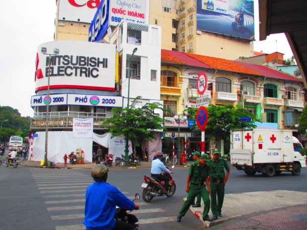 the men in green uniforms are to be found at major intersections to help tourists safely cross the road